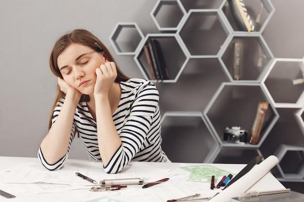 Bliska portret śpiącego, uroczego młodego europejskiego niezależnego inżyniera dziewczyna zasypia w miejscu pracy podczas przygotowań do spotkania z liderem zespołu, aby porozmawiać o błędach w pracy