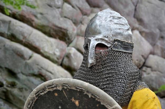 Bliska portret średniowiecznego rycerza w zbroi i hełmie.