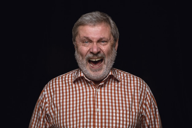 Bliska portret starszego mężczyzny na białym tle na czarnej ścianie. prawdziwe emocje męskiego modelu. płacz przez śmiech i uśmiech. wyraz twarzy, koncepcja ludzkich emocji.