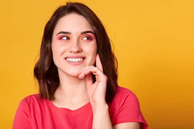 Bliska portret studio ślicznej uroczej damy odwracającej wzrok, trzyma rękę pod brodą, próbuje coś zrozumieć lub zapamiętać, ma jasny makijaż, pozowanie na białym tle nad żółtym