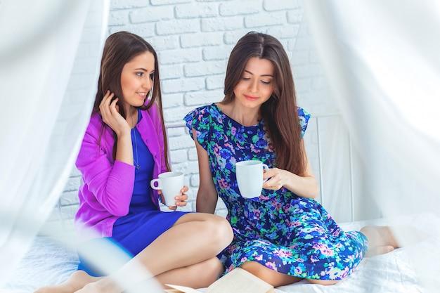 Bliska portret styl życia dwóch całkiem wesoły dziewcząt trzyma filiżankę kawy.