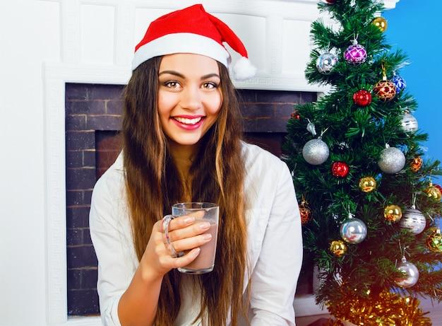 Bliska portret styl życia ładna brunetka kobieta pije gorącą czekoladę w sylwestra, ubrana w santa hat i siedząc przy kominku i ozdobione choinką. przytulna domowa atmosfera.