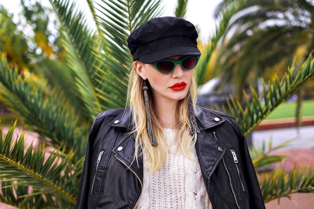Bliska portret stylowej blondynki pozuje w pobliżu palm w okresie zimowym, ubrana w skórzaną kurtkę, modne okulary przeciwsłoneczne retro, czapkę i długie kolczyki, delikatne kolory.