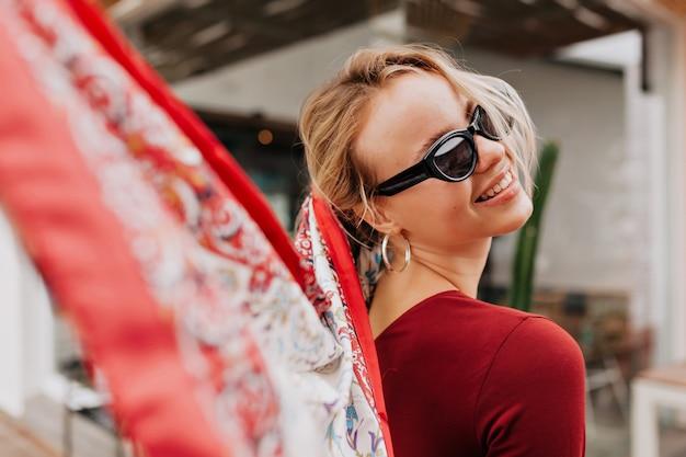 Bliska portret sympatycznej stylowej kobiety o blond włosach zawrócić i akcesoria