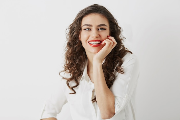 Bliska portret szczery uśmiechnięta atrakcyjna kobieta z białymi zębami na białym tle, długie kręcone włosy, biała bluzka, elegancki styl biznesowy, szczęśliwe pozytywne emocje, makijaż czerwona szminka