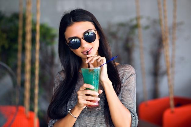 Bliska portret szczęśliwa ładna brunetka kobieta pije smaczny zimny koktajl, stylowy strój i lustrzane okulary przeciwsłoneczne, ciesz się jej weekendem, imprezą.