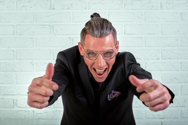 Bliska portret szczęśliwego młodego biznesmena w okularach ubranych w czarny garnitur pokazuje fajne ręce