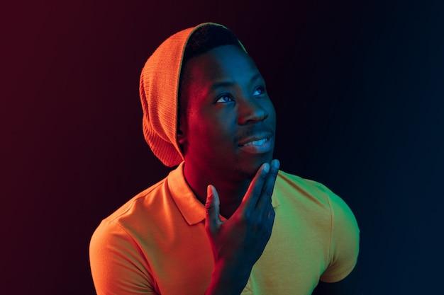 Bliska portret szczęśliwego młodego człowieka afroamerykanów, uśmiechając się na tle czarnego studia neonowego