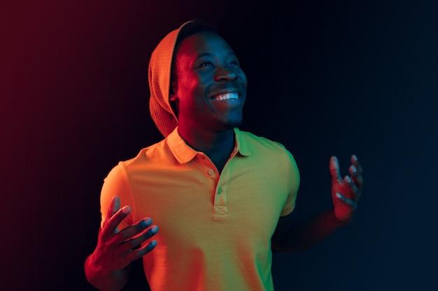 Bliska portret szczęśliwego młodego człowieka uśmiechniętego przeciwko czarnemu neonowemu studiu