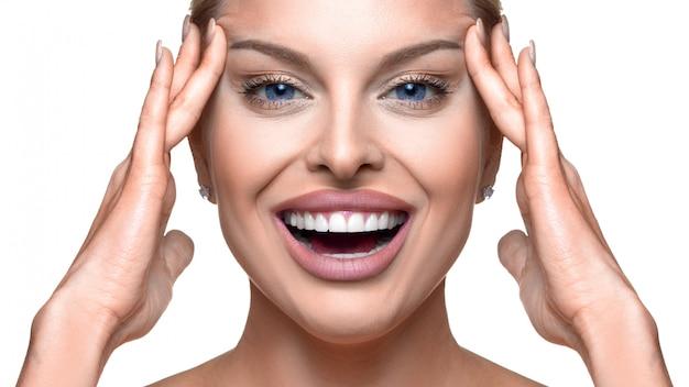 Bliska portret szczęśliwej kobiety dotykając jej twarzy. koncepcja pielęgnacji skóry i anti age.