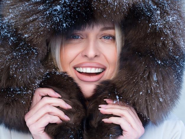 Bliska portret szczęśliwej kobiety w futrzany kaptur patrząc na kamery. portret mroźny zimowy.