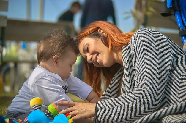 Bliska portret szczęśliwej mamy i dziecka w ogrodzie