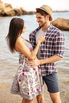 Bliska portret szczęśliwej młodej pary hipster zakochanych, stojąc na plaży i przytulanie