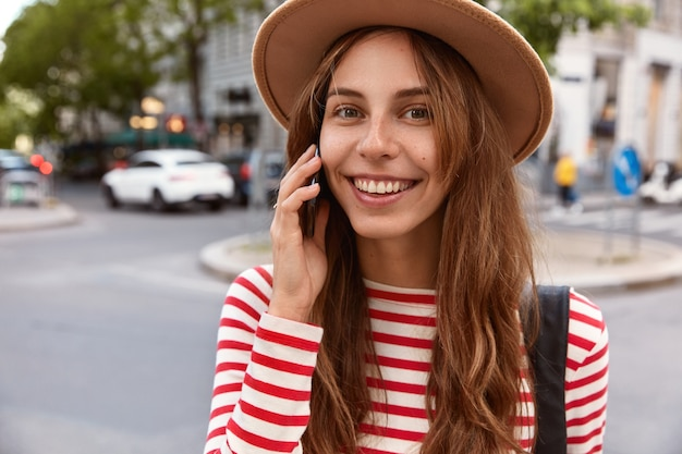 Bliska portret szczęśliwej modelki dzwoni do operatora usługi, spaceruje w centrum miasta, korzysta z połączenia w roamingu, lubi podróż za granicę, ma długie włosy