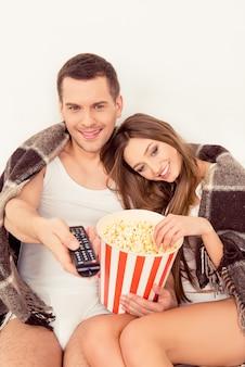 Bliska portret szczęśliwej rodziny, oglądanie telewizji i jedzenie popcornu