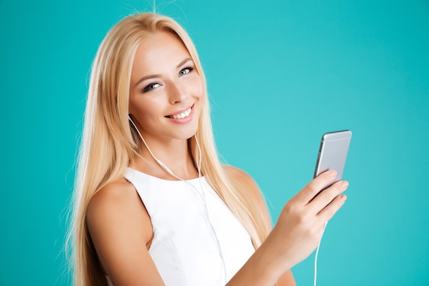Bliska portret szczęśliwej uśmiechniętej dziewczyny ze słuchawkami i telefonem komórkowym na białym tle na niebieskiej ścianie