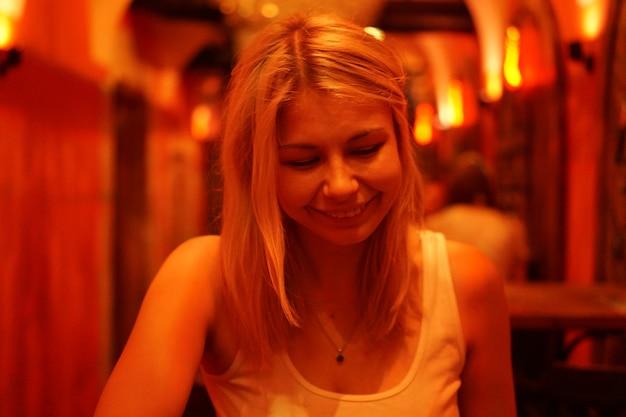 Bliska portret szczęśliwej uśmiechniętej kobiety w barze lub kawiarni z neonami