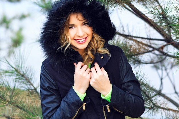 Bliska portret szczęśliwej wesołej kobiety, która bawi się sama w zimowy dzień, ma jasny makijaż rudych włosów i niesamowity uśmiech. noszenie ładnej stylowej kurtki z futrem, neonowego swetra. nastrój świąteczny.