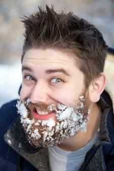 Bliska portret szczęśliwy młody brodaty mężczyzna w zimnie w zimowym lesie o zachodzie słońca. zabawny facet się uśmiecha.