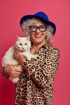 Bliska portret szczęśliwy pomarszczony modnej babci z pięknym kotem