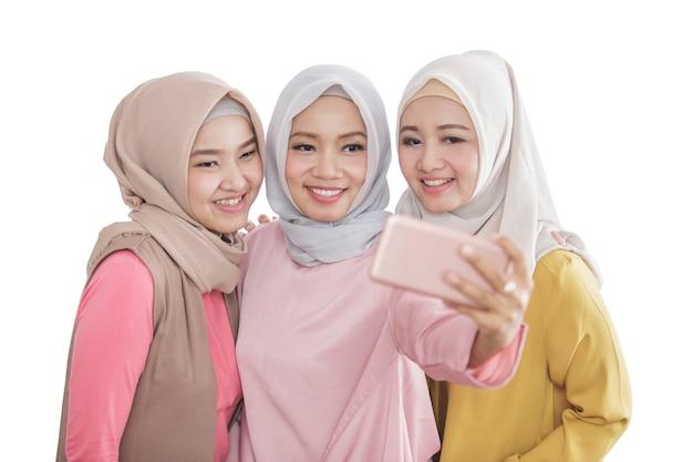 Bliska portret trzech pięknych rodzeństwa biorąc selfie za pomocą aparatu telefon komórkowy na białym tle