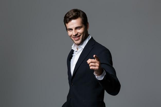 Bliska portret udanego młodego biznesmena ubranego w garnitur na białym tle nad szarą ścianą, wskazując palcem