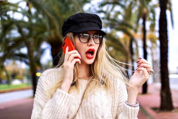 Bliska portret ulicy całkiem eleganckiej stylowej kobiety mówiącej przy swoim smartfonie, podekscytowana zaskoczonymi emocjami, wydrukuj biznesową kobietę, pozującą przed palmami, wiosna.