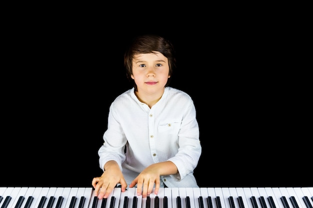 Bliska portret uroczego chłopca na sobie elegancką białą koszulę.