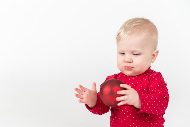 Bliska portret uroczego dziecka w czerwonej koszuli z czerwoną piłką