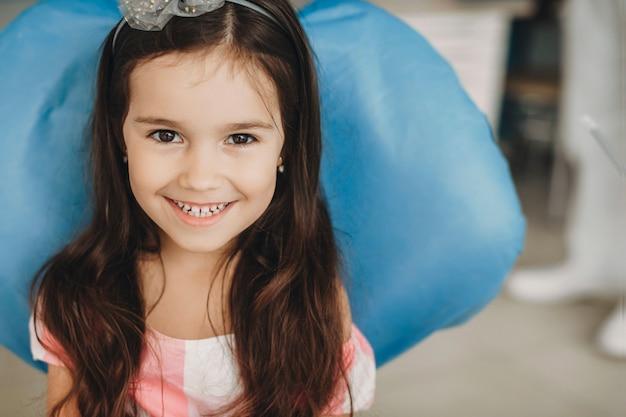 Bliska portret uroczej dziewczynki, śmiejąc się, patrząc na kamery, siedząc w fotelu stomatologii.