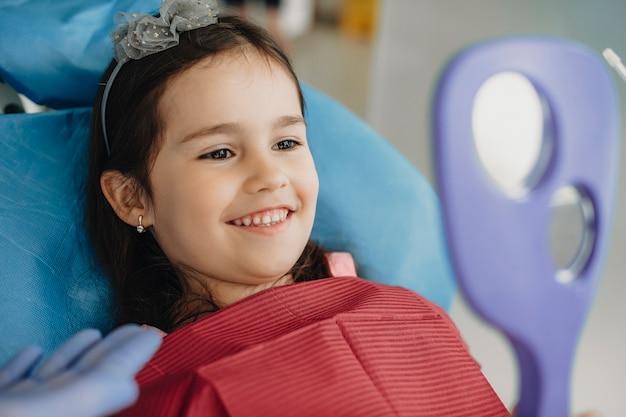 Bliska portret uroczej dziewczynki uśmiechając się, patrząc w lustro po operacji zębów w stomatologii dziecięcej.