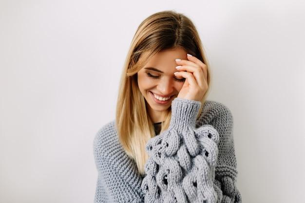 Bliska portret uroczej kobiety o blond włosach zakrywających twarz i uśmiechając się z zamkniętymi oczami