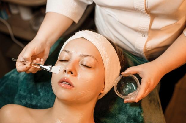 Bliska portret uroczej kobiety rasy kaukaskiej wykonującej maskę przeciwstarzeniową z kwasem hialuronowym przez kosmetologa w centrum odnowy biologicznej.