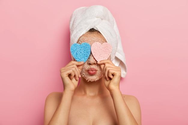 Bliska portret uroczej kobiety ukrywa twarz za pomocą dwóch kosmetycznych gąbek, ma złożone usta, nosi biały miękki ręcznik, ma nagie ciało