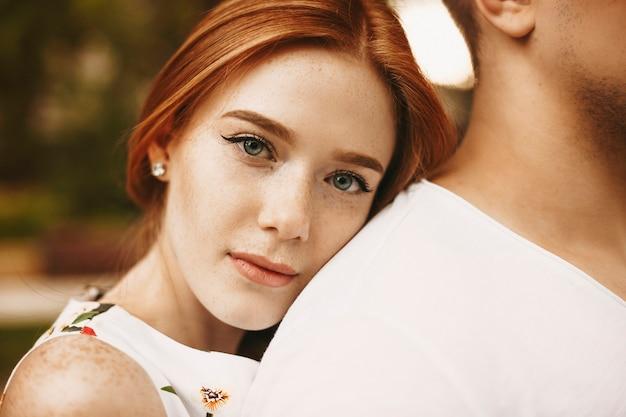 Bliska portret uroczej kobiety z rudymi włosami z piegami i szarymi oczami patrząc na kamerę poważnie, jednocześnie opierając głowę na plecach swojego chłopaka na zewnątrz.