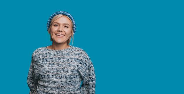 Bliska portret uroczej młodej kobiety patrząc na kamery, uśmiechnięty, ubrany na niebiesko na niebieskim tle.