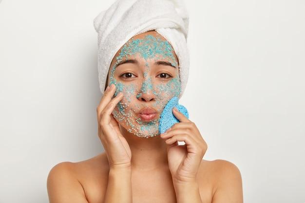 Bliska portret uroczej młodej kobiety z założonymi ustami, wykonuje procedurę peelingu czystości, ma ręcznik na głowie, nakłada granulki soli morskiej na twarz, trzyma gąbkę do wycierania skóry