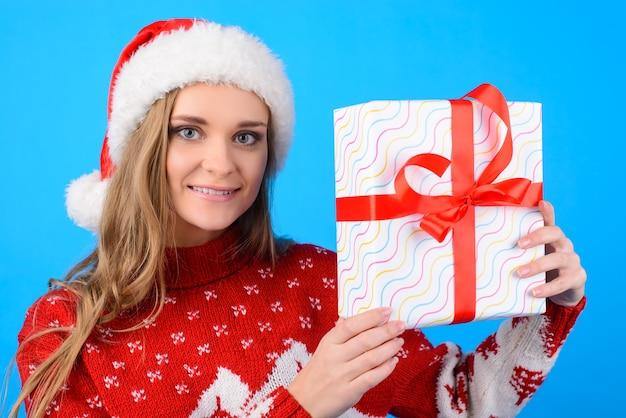 Bliska portret uroczy szczęśliwy ładny uśmiechający się piękna dziewczyna pokazując i trzymając w ręce obecne pudełko, na białym tle na niebieskim tle