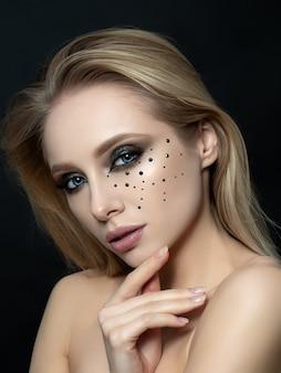 Bliska portret uroda młodej kobiety z piękny makijaż moda dotyka jej twarzy. nowoczesny makijaż mody. długie rzęsy, brązowe smokey eyes, czarne cyrkonie.