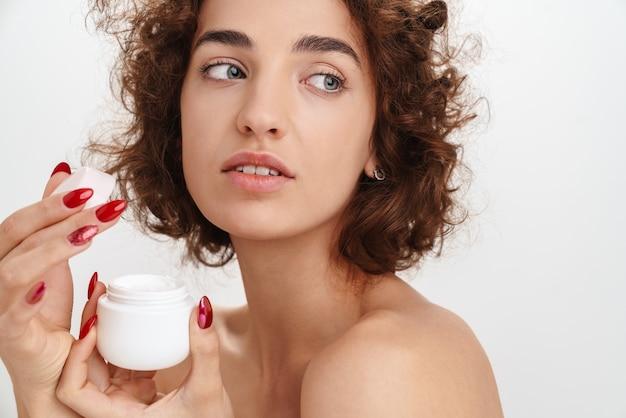 Bliska portret urody atrakcyjnej młodej kobiety topless z krótkimi, kręconymi brązowymi włosami na białym tle nad białą ścianą, pokazując pojemnik z kremem do twarzy