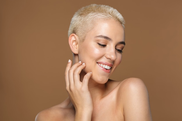 Bliska portret urody atrakcyjnej uśmiechniętej młodej blondynki z krótkimi włosami pozuje na białym tle na brązowym, z zamkniętymi oczami