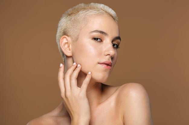 Bliska portret urody atrakcyjnej uśmiechniętej młodej blondynki z krótkimi włosami pozuje na brązowym tle