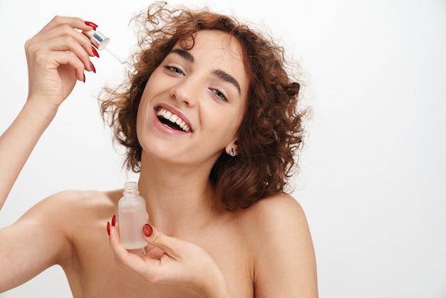 Bliska portret urody atrakcyjnej uśmiechniętej młodej kobiety topless z krótkimi, kręconymi brązowymi włosami na białym tle nad białą ścianą, pokazującą krople oleju do twarzy