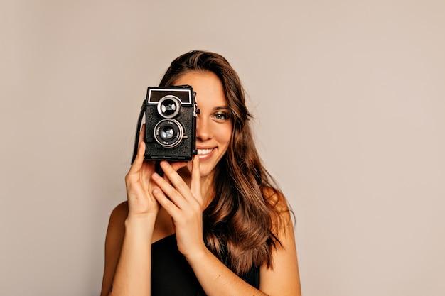 Bliska portret uśmiechnięta ładna kobieta z długimi kręconymi włosami i jasny makijaż pozowanie z aparatem retro na beżu