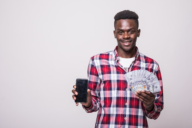 Bliska portret uśmiechniętego mężczyzny afrykańskiego pokazano pusty ekran telefonu komórkowego, trzymając kilka banknotów pieniędzy na białym tle
