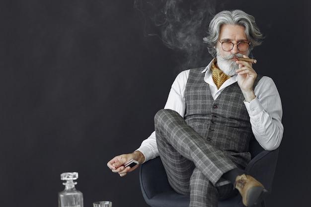 Bliska portret uśmiechniętego staromodnego człowieka. dziadek z cygarem i whisky.