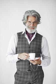 Bliska portret uśmiechniętego staromodnego człowieka. dziadek z kubkiem herbaty.