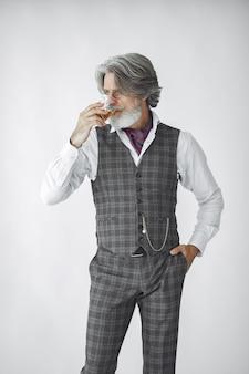 Bliska portret uśmiechniętego staromodnego człowieka. dziadek ze szklanką whisky.