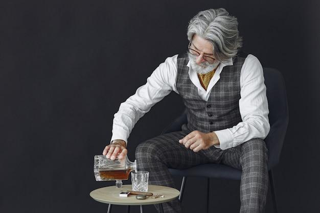Bliska portret uśmiechniętego staromodnego człowieka. pan siedzący na krześle. dziadek ze szklanką whisky.