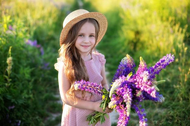 Bliska portret uśmiechniętej dziewczynki w słomkowym kapeluszu iz dużym bukietem łubinów.